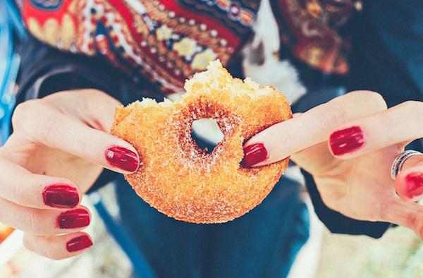 woman holding a sugar doughnut