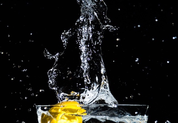 lemon splashing into bowl of water