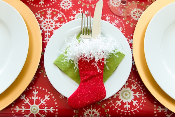 white plate and red christmas stocking on a red snowflake tablecloth