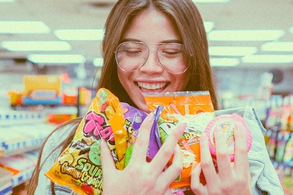 SMILING WOMAN HOLDING BAGS OF SWEETS
